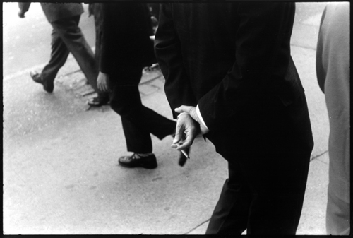 man in a suit holding cigarette